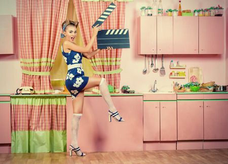 Beautiful pin-up girl on a pink kitchen posing with cinema clapper board. Retro style. Show business. Cinematography. Stock Photo