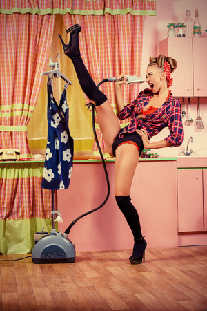 sexy housewife: Charming pin-up girl ironing her dress and singing on a glamorous pink kitchen. Retro style. Fashion. Stock Photo