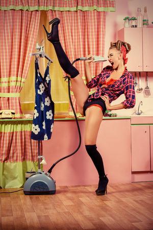 pin up vintage: Charming pin-up girl stirare il vestito e cantando su una cucina rosa glamour. Stile retrò. Fashion.