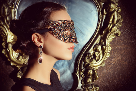 masquerade masks: Close-up portrait of a beautiful woman in venetian mask. Carnival, masquerade. Jewellery, gems. Stock Photo