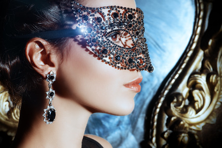masked: Close-up portrait of a beautiful woman in venetian mask. Carnival, masquerade. Jewellery, gems. Stock Photo