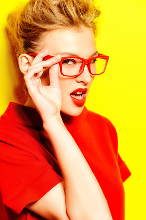 Close-up portrait of a stunning female model in red dress and elegant spectacles posing over yellow background. Beauty, fashion, optics. Stock Photo