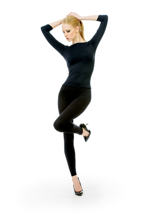 tight fitting: Full length portrait of a beautiful slender female model in black fitting clothing posing over white background. Beauty, fashion. Body care. Isolated over white.