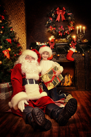 home decorated: Portrait of Santa Claus with a boy sitting at home decorated for Christmas. Christmas scene.