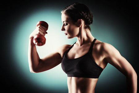 weight lifting: Slender young woman with beautiful athletic body doing exercises with dumbbells. Fitness, bodybuilding. Health care.