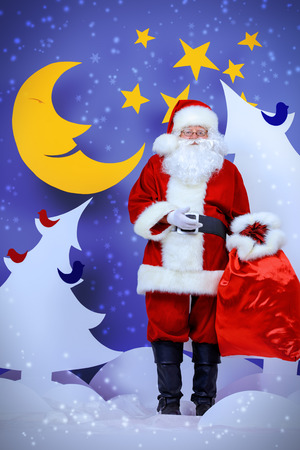 full length: Santa Claus standing with his bag of giftsin a cartoon fairy snowy forest. Full length portrait.