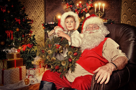 cor: Santa Claus in his everyday clothes in Christmas home d�cor. Happy little boy helps Santa Claus get ready for Christmas.