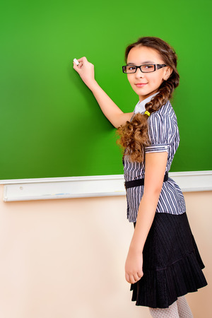 Smiling schoolgirl performs the task at the blackboard. Education. Stock Photo