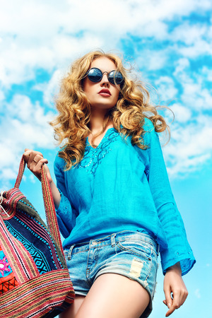 hippie: Gorgeous young woman with beautiful wavy hair wearing casual blouse and jeans shorts posing outdoor. Fashion shot.