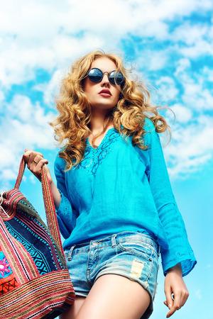 mujer hippie: Hermosa mujer joven con el pelo hermoso ondulado llevaba blusa casual y jeans cortos posando al aire libre. Disparo de moda.
