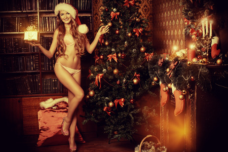 Tall slender girl in sexy lingerie alluring by the fireplace in the Christmas atmosphere. Full length portrait.