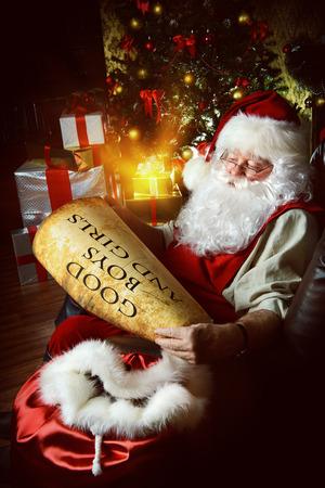 papa noel: Santa Claus vestido con su ropa de casa que se sientan en la sala junto a la chimenea y el �rbol de Navidad. �l est� leyendo una lista de buenos muchachos y muchachas. Navidad. Decoraci�n.