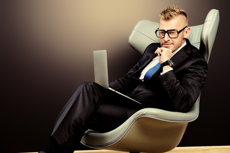 luxurious interior: Imposing mature man in elegant suit sitting on a leather chair in a modern luxurious interior and working on a laptop. Fashion. Business. Stock Photo