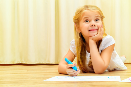 left handed: Cute girl on a floor and drawing on paper with colorful pens