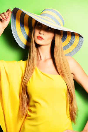 Portrait of a stunning fashionable lady in bright yellow dress posing over  green background. Beauty, fashion concept. Colors of summer. Stock Photo