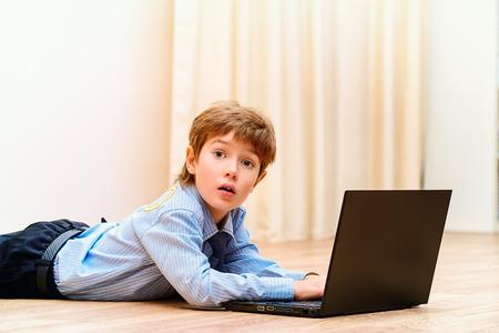 schoolkid search: Muchacho lindo acostado en un piso en casa con su ordenador port�til. Ordenador de casa. Educaci�n. Foto de archivo