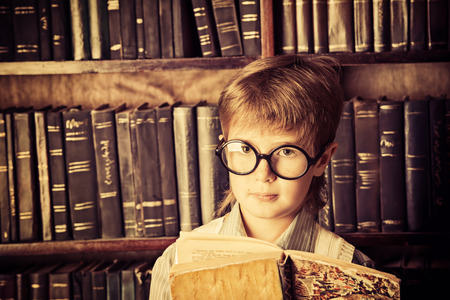 scientific literature: Smart boy stands in the library by the bookshelves with many old books. Educational concept. Science. Vintage style.