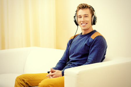 Handsome young man at home, listening to music in headphones and smiling. photo