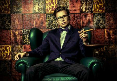 Gut aussehender junger Mann im eleganten Anzug raucht eine Zigarre. Er ist auf einem Ledersessel sitzen in einem luxuriösen Innenraum.
