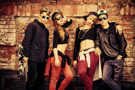 hip hop girl: Group of young modern people posing together with fun. Urban lifestyle. Hip-hop generation.