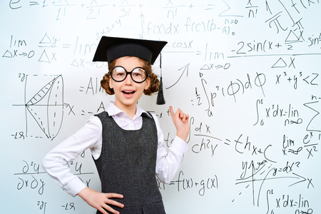 achiever: Happy smart schoolgirl in big glasses and academic hat performs the task at the blackboard. Education. Stock Photo