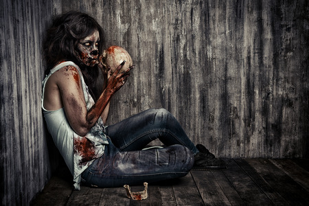 dead girl: Frightening bloody zombie girl with a skull. Halloween.