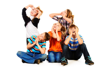 natural wonders: Group of cheerful children sitting together and expressing surprise. Isolated over white. Stock Photo