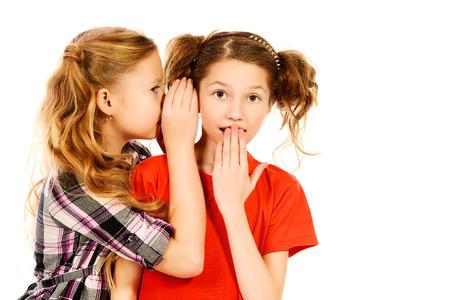 niños platicando: Dos chicas susurrando entre sí acerca de algo. Aislado en blanco.