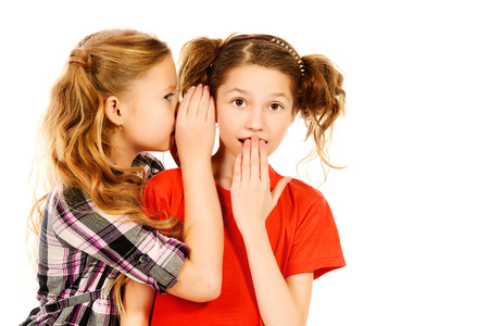 Two girls whispering to each other about something. Isolated over white. photo