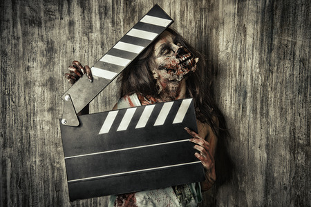holiday movies: Filming a horror movie. Female zombie holding clapper board. Cinematography. Halloween.