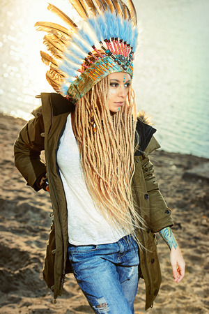 indian headdress: Fashion shot of a beautiful girl in style of the American Indians. Western style. Jeans fashion. Stock Photo
