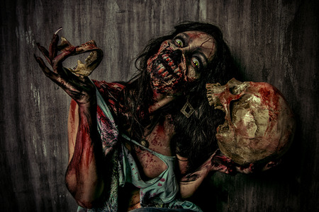 massacre: Frightening bloody zombie girl with a skull. Halloween.