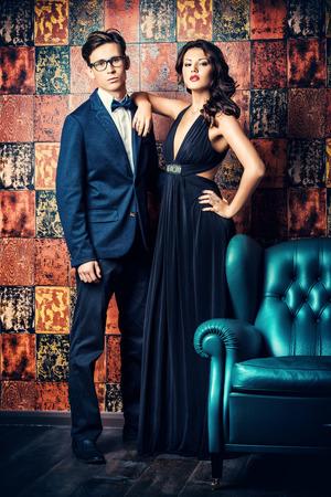 suit: Magnífica hermosa pareja en vestidos de noche elegantes en un interior clásico. Moda, glamour.