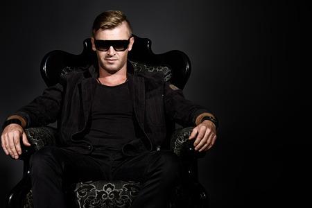 traje formal: Retrato de un hombre guapo masculino en elegante traje negro, sentado en una silla en un estilo de �poca cl�sica. Foto de archivo