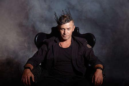 trono: Retrato de un hombre guapo masculino en elegante traje negro, sentado en una silla en un estilo de época clásica. Foto de archivo