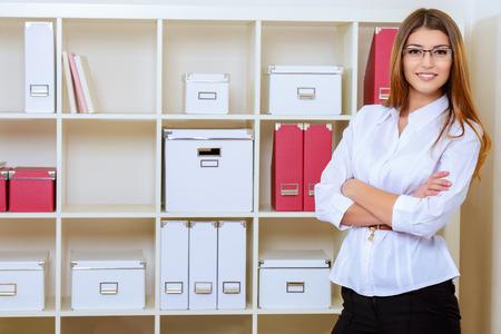 business attire teacher: Portrait of a beautiful smiling businesswoman working in a modern office.