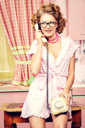 chitchat: Beautiful sexy pin-up girl talking on the phone on a pink kitchen. Fashion.