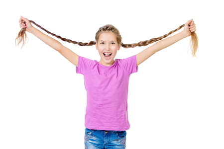 beautiful teen girl: Cheerful teen girl in bright casual clothes holds her long braids. Hair, haircare. Studio shot. Isolated over white. Stock Photo