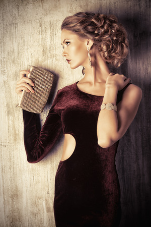 clutch: Charming young woman wearing elegant evening dress and beautiful hairstyle. Jewellery.  Fashion shot. Stock Photo