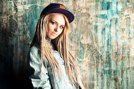 naughty woman: Modern teenage girl with blonde dreadlocks. Jeans style. Modern generation.