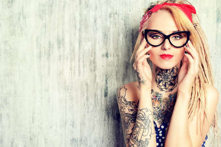 blond: Close-up portrait of a modern pin-up girl wearing old-fashioned polka-dot dress and spectacles and modern dreadlocks. Fashion shot. Tattoo.