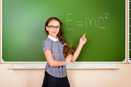 cute teen girl: Школьница в очках стоит на доске во время урока физики. Образование.