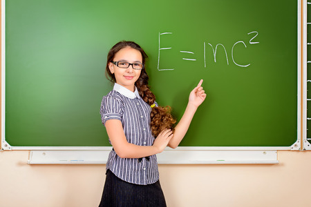 cute teen girl: A schoolgirl in spectacles stands at the blackboard during a physics lesson. Education. Stock Photo