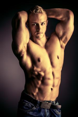 Muscular bodybuilder man posing over dark background. Mens beauty. Sports.