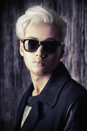 Portrait of a handsome male model with blond hair wearing black jacket and sunglasses. Urban style. Fashion. photo