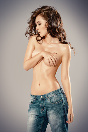 beautiful breasts: Sexual shirtless young woman alluring in jeans. Studio shot. Beauty, fashion.