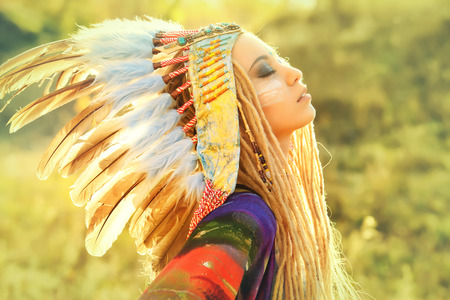 western clothing: Close-up portrait of a beautiful girl wearing native american indian chief headdress. Western style. Jeans fashion.