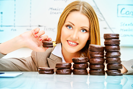 confectionary: Beautiful businesswoman posing with cookies laid out in the form of diagrams. Business concept. Confectionary. Food industry.