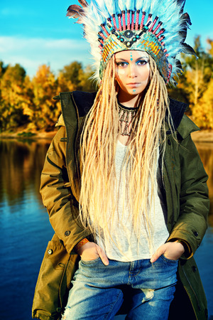 female face: Fashion shot of a beautiful girl in style of the American Indians. Western style. Jeans fashion. Stock Photo