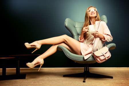 modelos posando: Retrato de una bella modelo de moda sentado en una silla de estilo Art Nouveau. Interior, muebles. Foto de archivo